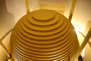 """image credit: © Guillaume Paumier / Wikimedia Commons; <a href=""""http://en.wikipedia.org/wiki/Image:Tuned_mass_damper_-_Taipei_101_-_Wikimania_2007_0224.jpg"""" target=""""_blank"""">image source</a>; <a href=""""http://www.physicstogo.org/images/features/Tuned-Mass-Damper-large-7-0.jpg"""" target=""""_blank"""">larger image</a>"""